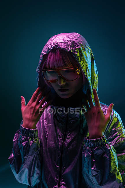 Trendy young Japanese woman with purple hair standing in silver hoodie jacket and red sunglasses on blue background — Stock Photo