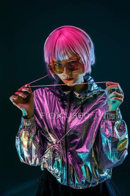 Jeune femme japonaise à la mode avec le cheveu pourpre restant dans la veste argentée étincelante et les lunettes de soleil rouges sur le fond bleu — Photo de stock