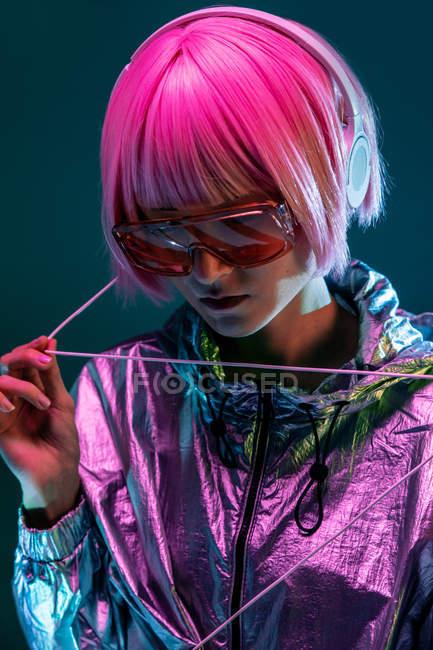 Trendy giovane donna giapponese con i capelli viola in piedi in giacca argento scintillante e occhiali da sole rossi su sfondo blu — Foto stock