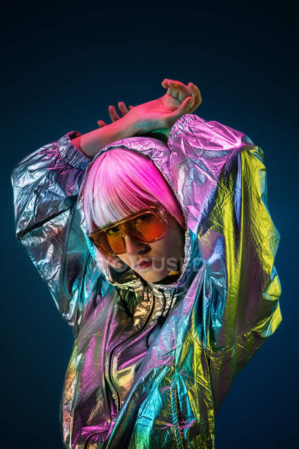 Trendy young Japanese woman with purple hair standing in sparkly silver jacket and red sunglasses on blue background — Stock Photo