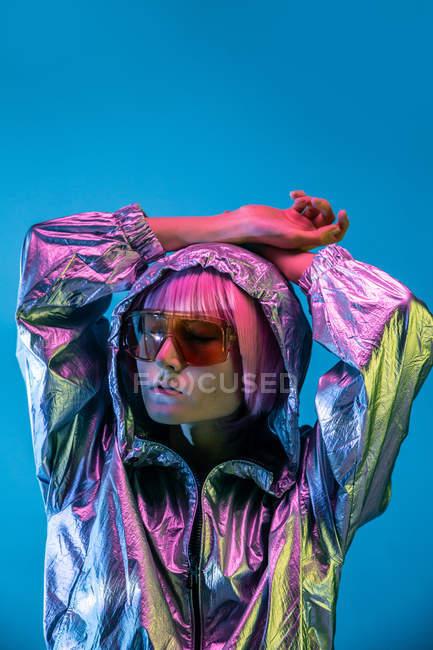 Модні молоді Японські жінки з фіолетовим волоссям стоячи в блискучий Срібний Жакет і червоні сонцезахисні окуляри на синьому фоні — стокове фото