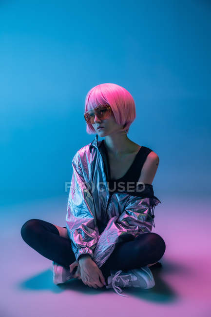 Модні молоді Японські жінки з фіолетовим волоссям і червоними сонцезахисні окуляри сидять на синьому фоні — стокове фото