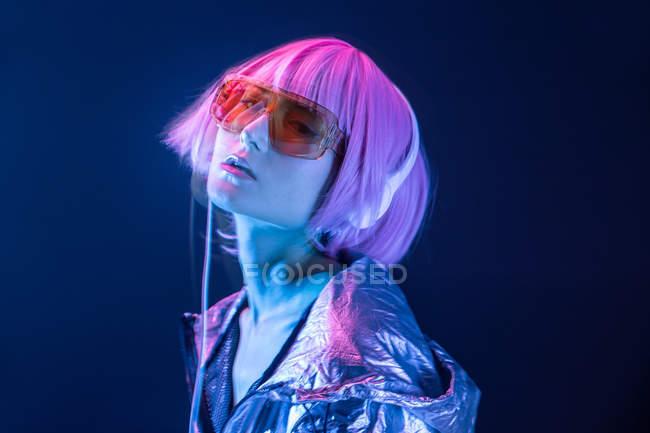 Sensual japonesa joven bonita mujer en gafas de sol rojas y auriculares posando sobre fondo oscuro - foto de stock