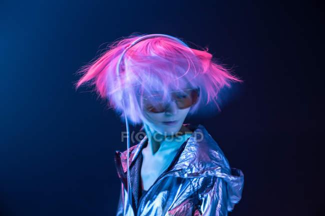 Giovane donna asiatica subculturale con capelli rosa sparsi e giacca d'argento che balla ascoltando musica in cuffia — Foto stock