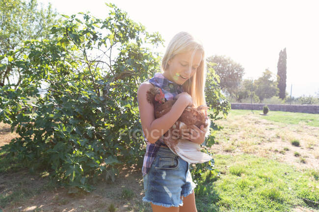 Teen girl and in checkered shirt and denim short petting hen while standing near green bushes on sunny day on farm — Stock Photo