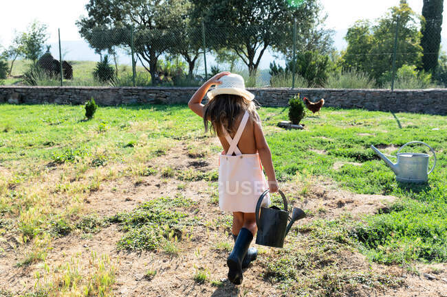 Little girl in dress and hat watering small bush while helping in garden on sunny day on farm — Stock Photo