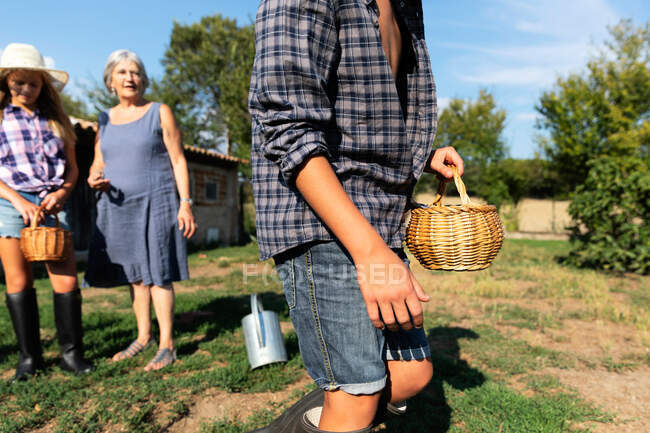 Grandmother near grandchildren on sunny day on ranch feeding chickens — Stock Photo