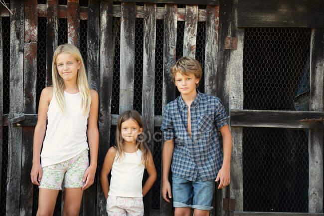 Мальчик и две девочки в повседневных нарядах улыбаются и стоят возле громоздкого деревянного сарая, проводя время на ферме — стоковое фото