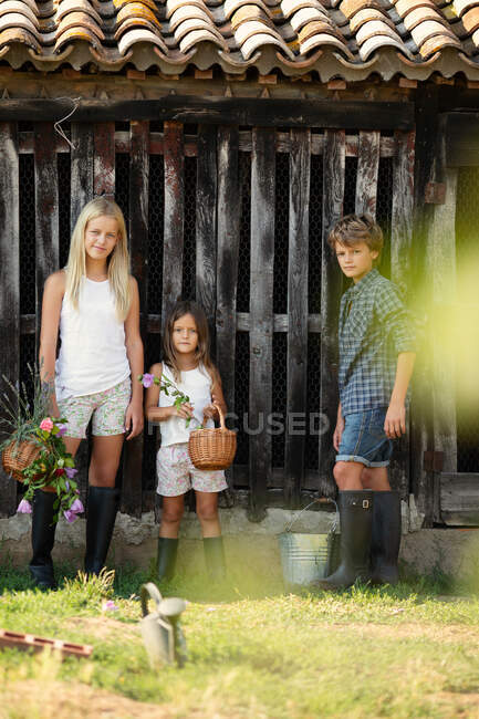 Boy and two girls in casual outfits smiling and standing near grungy wooden barn while spending time on farm — Stock Photo