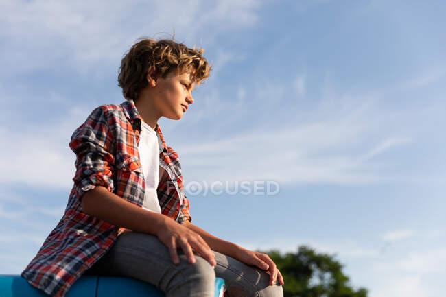 Вид сбоку мальчика в повседневной одежде, который смотрит в сторону, сидя на голубом трамвае на фоне облачного неба в солнечный день на ферме — стоковое фото