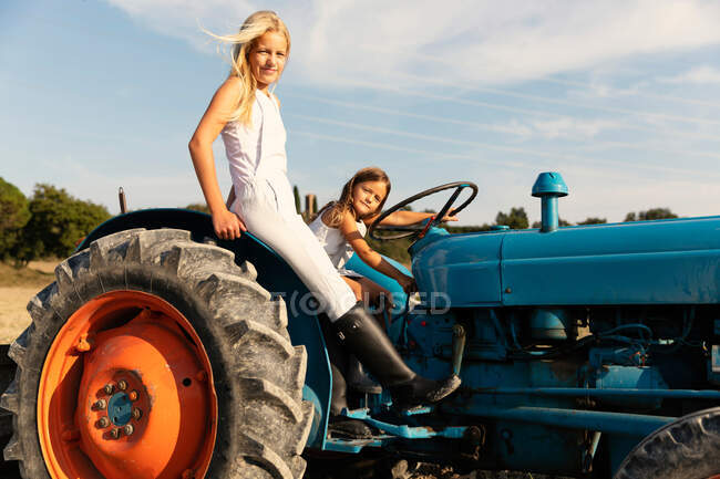 Side view of happy girls in casual outfits driving blue tractor on agricultural field on sunny day on farm — Stock Photo