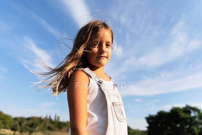 Молодая девушка позирует на солнце, глядя в камеру. — стоковое фото