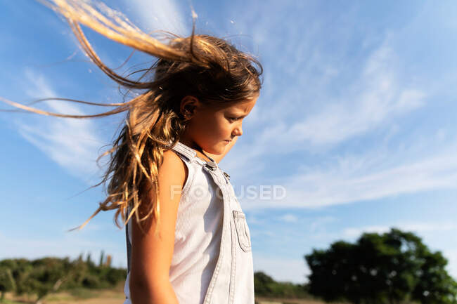 Молодая девушка позирует в солнечном свете, отводя взгляд — стоковое фото