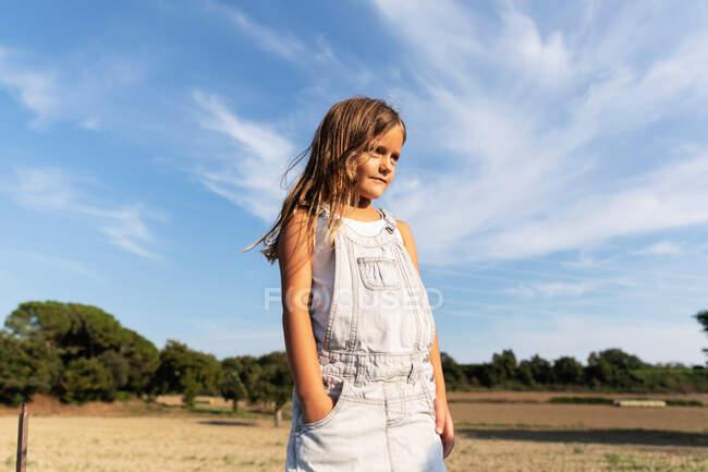 Молода дівчина, що кидає на сонці, озирається — стокове фото