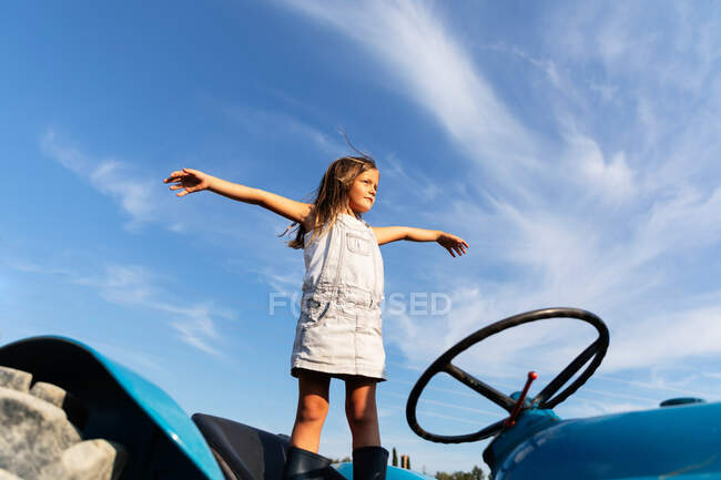 Little girl in denim dress stretching out arms while standing on tractor against cloudy sky on farm — Stock Photo