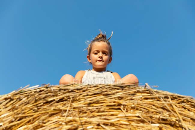 Menina olhando para a câmera enquanto sentado no rolo de grama seca contra o céu azul sem nuvens no dia ensolarado na fazenda — Fotografia de Stock