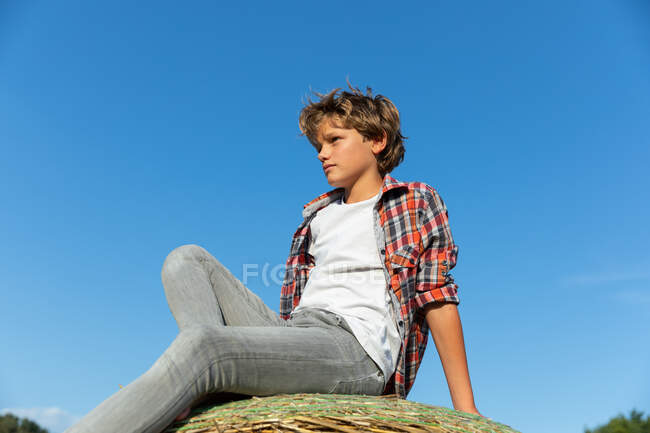 Young boy looking at away while sitting on roll of dry grass against cloudless blue sky on sunny day on farm — Stock Photo