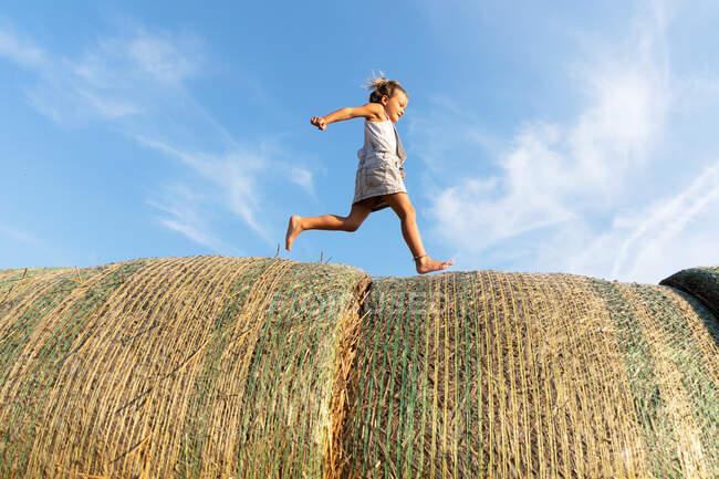 Vista lateral de la chica descalza corriendo sobre rollos de hierba seca contra el cielo azul nublado en el día soleado en la granja - foto de stock