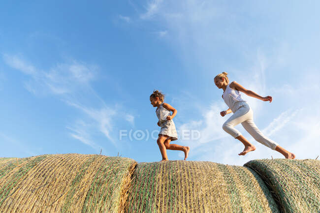 Side view of three kids running on rolls of straw together against cloudy blue sky in agricultural field — Stock Photo