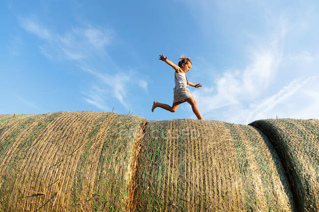 Side view of barefoot girl running on rolls of dried grass against cloudy blue sky on sunny day on farm — Stock Photo