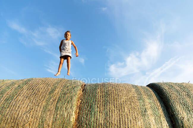 Босоногая девушка, бегущая по рулонам сухой травы на фоне облачного голубого неба в солнечный день на ферме — стоковое фото