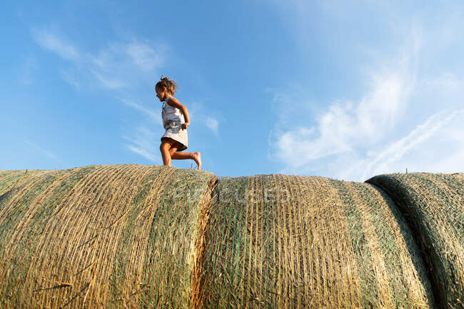 Босонога біжить по сушеній траві проти темно-синього неба в сонячний день на фермі. — стокове фото