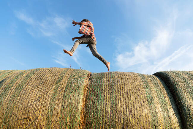 Side view of barefoot boy running on rolls of dried grass against cloudy blue sky on sunny day on farm — Stock Photo