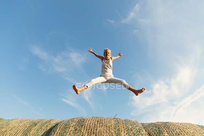 Босоніж стрибає на сухих травах проти хмарного блакитного неба в сонячний день на фермі. — стокове фото