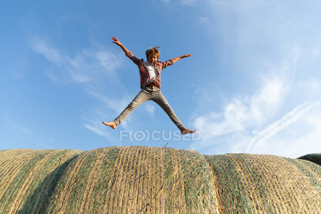 Barefoot boy jumping on rolls of dried grass against cloudy blue sky on sunny day on farm — Stock Photo