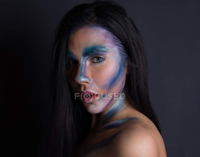 Young attractive woman with painting blue and silver color face on black background looking at camera — Stock Photo