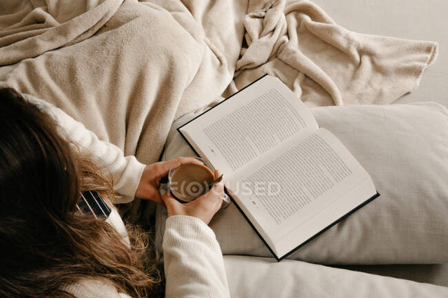 Unrecognizable woman sitting on the bed reading a book and drinking coffee — Stock Photo