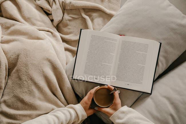 Неузнаваемая женщина сидит на кровати, читает книгу и пьет кофе. — стоковое фото