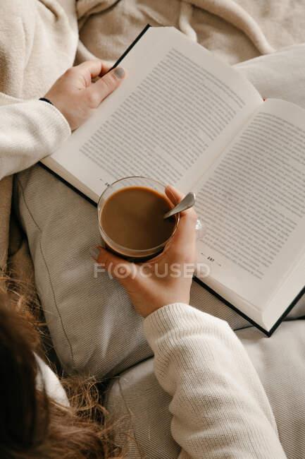 Невпізнавана жінка сидить на ліжку і читає книжку і п