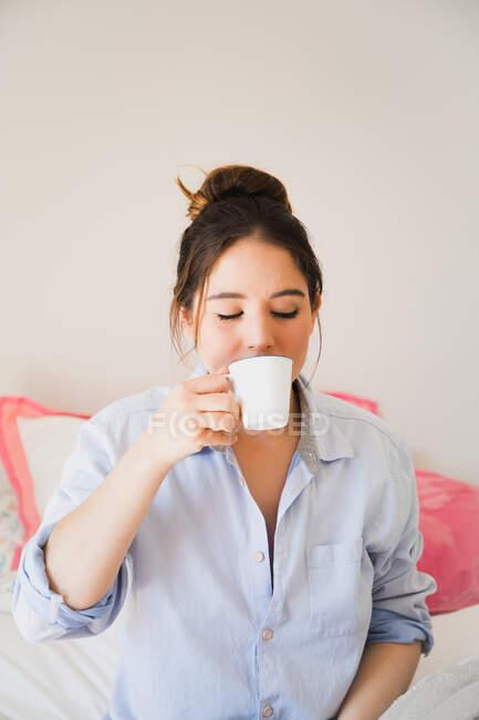 Sognante bella giovane donna bere caffè rinfrescante dalla tazza mentre seduto sul letto con gli occhi chiusi — Foto stock
