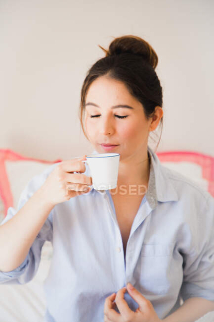 Dreamy beautiful young woman drinking refreshing coffee from mug while sitting on bed with closed eyes — Stock Photo