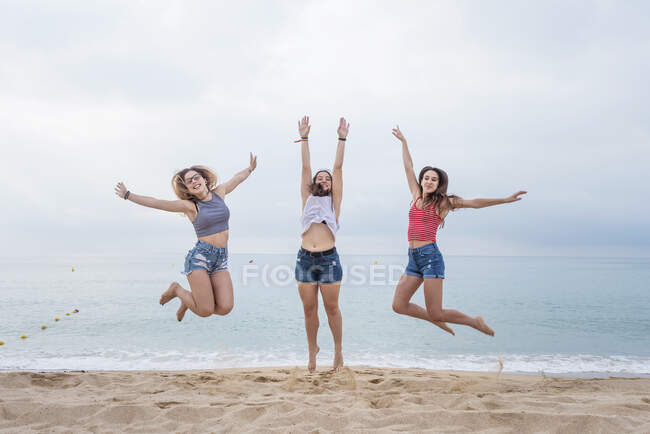 Front view of a group of three young smiling female friends jumping and having fun on the beach — Stock Photo