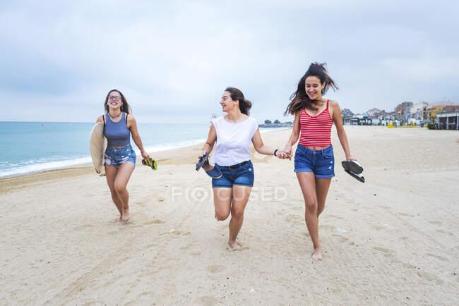 Grupo de três jovens amigas caminhando na praia — Fotografia de Stock