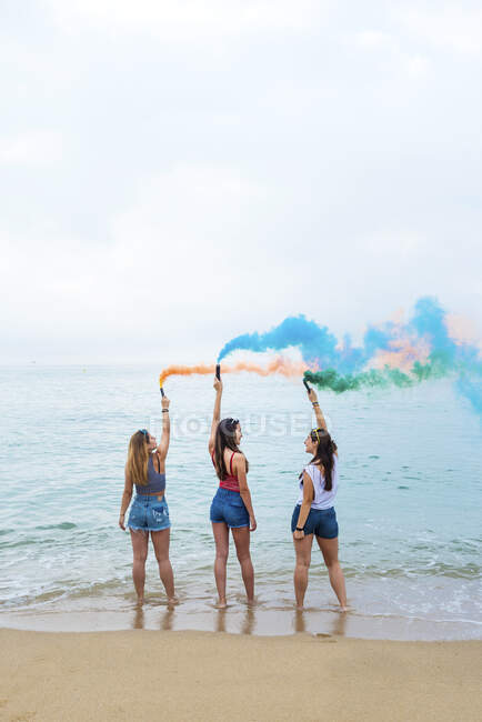 Happy teenage girls holding colored smoke bombs and having fun on the beach — Stock Photo