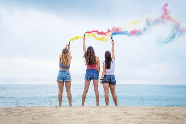 Felice ragazze adolescenti in possesso di bombe fumogene colorate e divertirsi sulla spiaggia — Foto stock