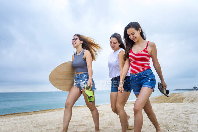 Group of three young female friends walking on seashore at the beach — Stock Photo