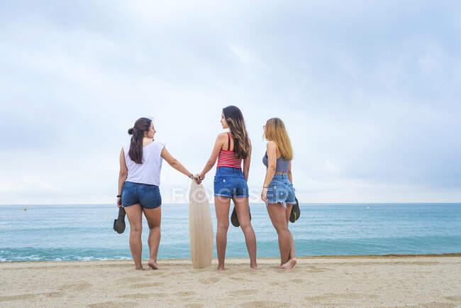 Vista posteriore di tre amiche in piedi sulla spiaggia insieme guardando dall'orizzonte — Foto stock
