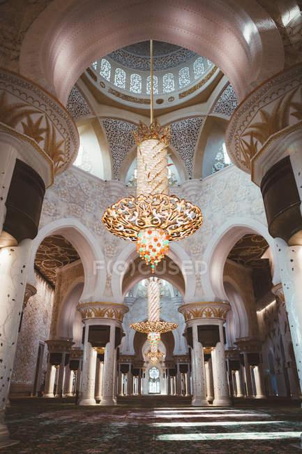 Von unten Blick auf Moschee-Interieur mit glühender goldener Lampe und Ziersäulen, Dubai — Stockfoto
