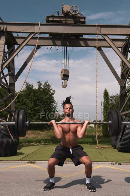 Black guy training with barbell in outdoor gym — Stock Photo