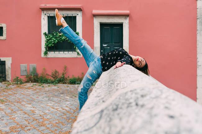 Giovane donna sottile casual che si estende sulla strada della città vecchia mentre balla con grazia — Foto stock