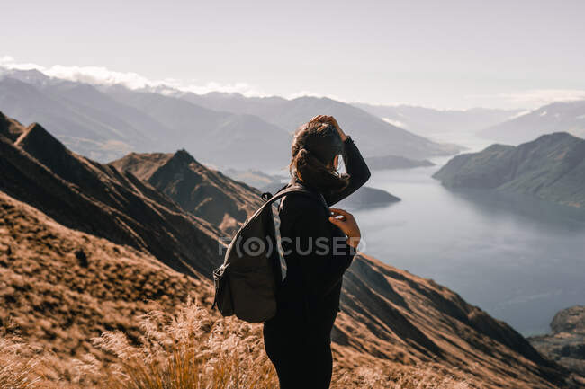 Back view of anonymous woman in coat standing on high peak of mountains in range looking away with hands on head - foto de stock