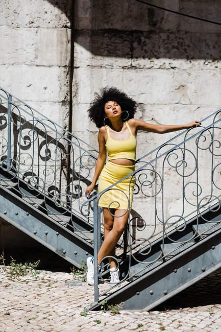 Afroamerikanerin im gelben Anzug steht und lehnt an Geländer vor städtischem Hintergrund — Stockfoto
