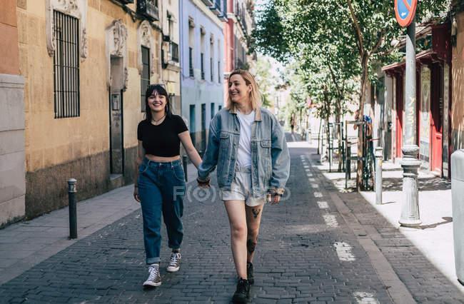Lesbiennes gaies tenant la main tout en marchant sur fond flou de la rue de la ville — Photo de stock