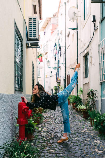 Young slim casual woman stretching on street of old city while dancing gracefully — Stock Photo
