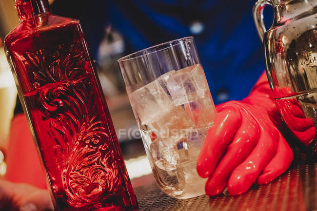 Bottle of red glass and glass full of ice cubes in hands on barman on bar counter — Stock Photo