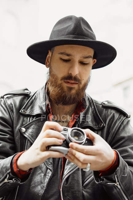 Young bearded handsome man in black hat and leather jacket taking photo in street — Stock Photo